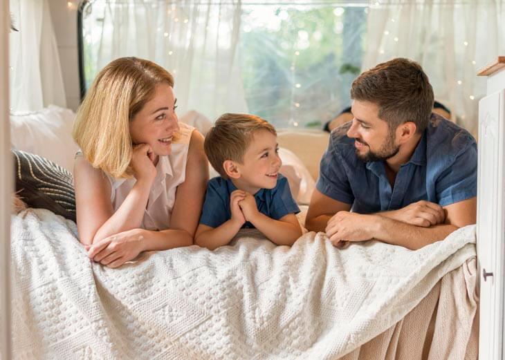 Família feliz estirada en la cama