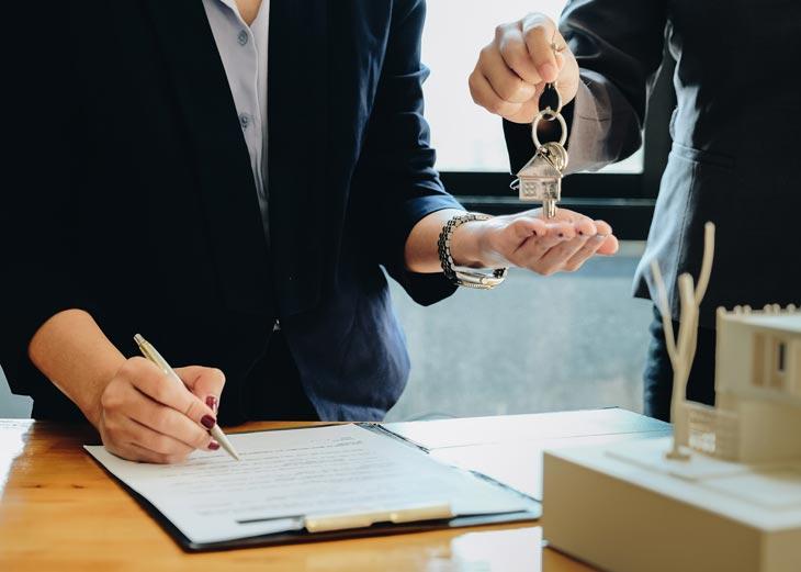 Chica firmando un contrato de alquiler mientras coje unas llaves