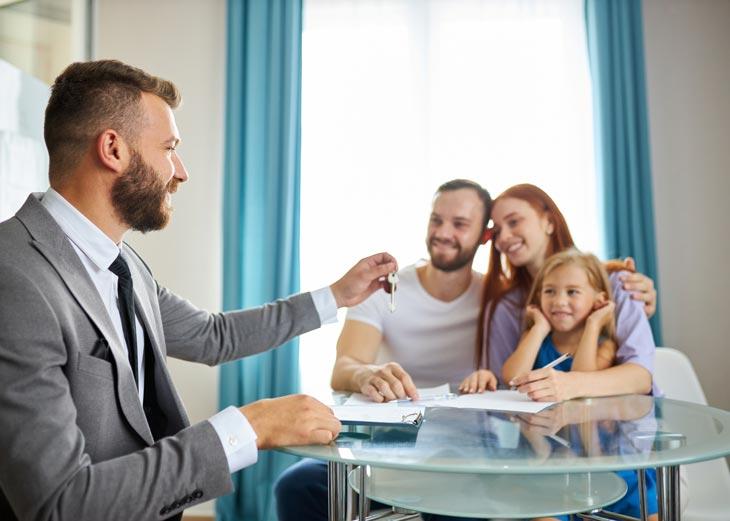 Chico dando llaves de una casa a una família
