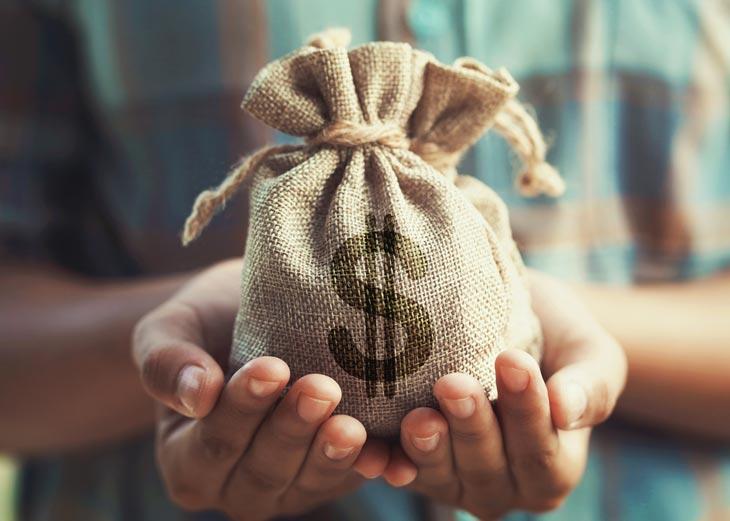 Persona aguantando un saco de dinero con las dos manos