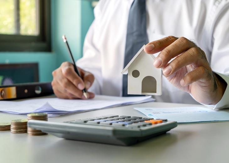 Señor con calculadora y una casa de juguete firmando un contrato