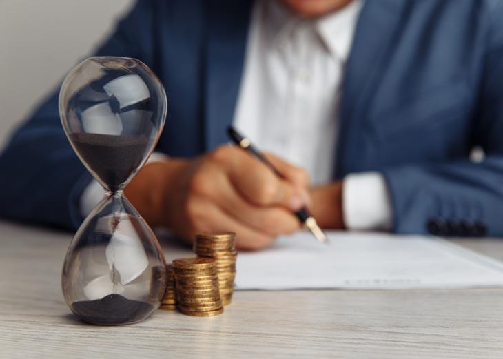 Reloj de arena y monedas con un señor de fondo firmando un contrato