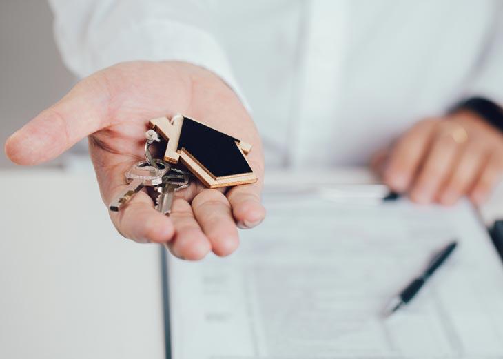 Persona con unas llaves y un llavero de una casa en la mano