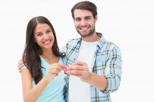 feliz-pareja-joven-mostrando-la-nueva-llave-de-la-casa_13339-46599
