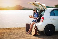 viajero-mujer-sentada-en-la-ventana-trasera-del-coche-y-mirando-el-mapa-cerca-del-lago_45381-102